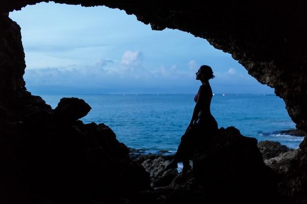 Frauenwartezeitsonnenuntergang in balinesse höhle am ozeanstrand