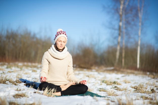 Frauenyoga, das in einer lotusposition auf schneebedecktem feld sitzt und meditiert.