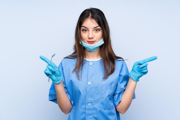Frauenzahnarzt, der werkzeuge über der blauen wand zeigt auf die seitenteile hat zweifel hält