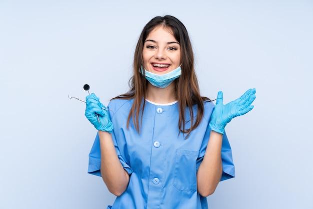 Frauenzahnarzt-holdingwerkzeuge über der blauen wand unglücklich und mit etwas frustriert