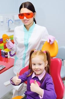 Frauenzahnarzt und kind-ein kleines mädchen mit dem roten haar im zahnmedizinischen stuhl zeigt ihre daumen