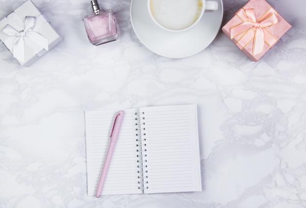 Frauenzubehör auf einer weißen marmortabelle. notizblock, stift und glas kaffee auf dem tisch und anderes weibliches kosmetisches zubehör. draufsicht, flache lage, kopienraum