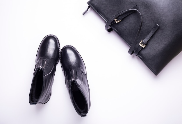 Frauenzubehör. schwarze stylische stiefel, schwarze luxusledertasche. ansicht von oben. flach liegen.