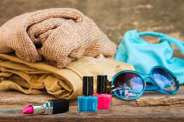 Frauenzubehör und -kosmetik auf altem hölzernem hintergrund