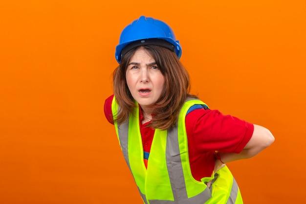 Frauingenieur, der bauweste und sicherheitshelm trägt, die unwohl fühlen, rückenschmerzen stehend, die über isolierter orange wand stehen