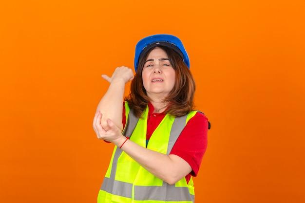 Frauingenieur, der konstruktionsweste und sicherheitshelm trägt, die unberührten berührenden ellbogen suchen, der schmerz hat, der über isolierter orange wand steht