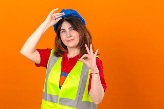 Frauingenieur in der bauweste und im sicherheitshelm, die zuversichtlich suchen, begrüßungsgeste zu machen, die helm berührt, der ok zeichen über isolierter orange wand tut