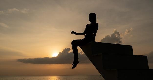 Frauschattenbild, das auf der treppe im sonnenuntergang sitzt.