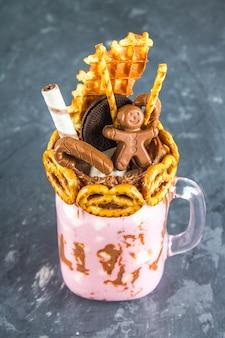 Freakshake aus rosa smoothie, sahne. monstershake mit einem schokoladenmann, zuckerrohr