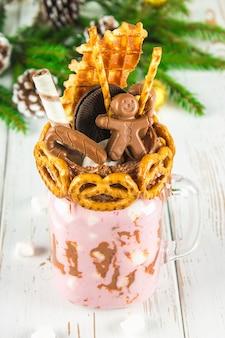 Freakshake aus rosa smoothie, sahne. monstershake mit einem schokoladenmann