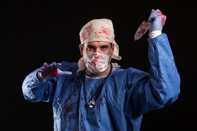 Freaky arzt in die kamera schaut auf schwarzem hintergrund isoliert. mann im doktorkostüm für halloween. gefährlicher arzt.