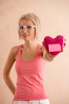 Freaky blondes mädchen mit den tragenden gläsern des kurzen haares, die plastikherz halten und kamera betrachten