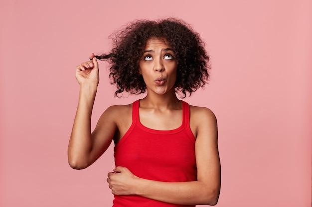 Freche afroamerikanerin mit afro-frisur, die nach oben schaut, rollte mit den augen, zeigt unschuld, gibt sich nicht schuldig, spielt mit lockigem dunklem haar, pfeift, isoliert