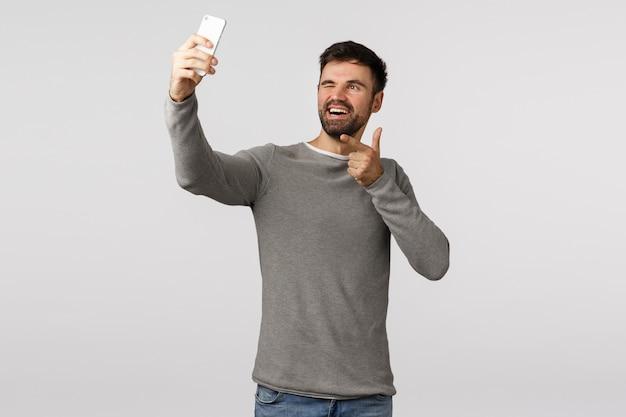 Freche, aufgeregte und sorglose junge mann bärtig, reisen ins ausland fotografieren, bilder online veröffentlichen, anwendungsfilter verwenden, smartphone nach oben halten und selfie nehmen, zwinkern