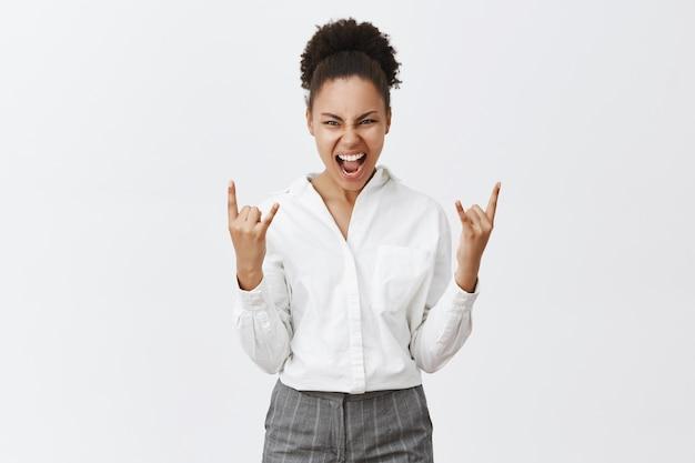 Freche erfolgreiche afroamerikanische geschäftsfrau, die rock-n-roll-geste zeigt, gewinnt oder triumphiert