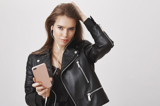 Freche frau in lederjacke, kopfhörer tragen und smartphone halten