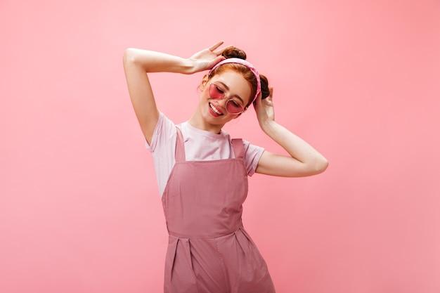 Freche frau mit sonnenbrille, weißem oberteil und rosa overall mit lächeln berührt ihre brötchen.