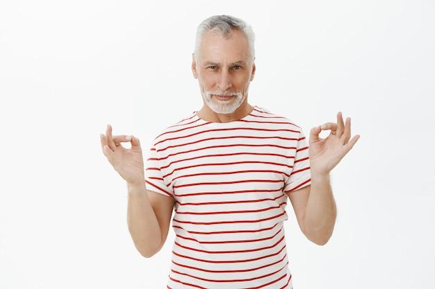 Freche gut aussehende bärtige ältere mann zeigen okay geste, alles unter kontrolle