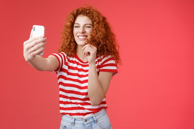 Freche, gut aussehende, stilvolle, charismatische rothaarige weibliche lockige frisur, die einen frechen ausdruck zwinkert, der flirtende, verworrene gesichter macht, halten das smartphone, das selfie-videonachrichten aufnimmt, spielen lustige gesichtsfilter.