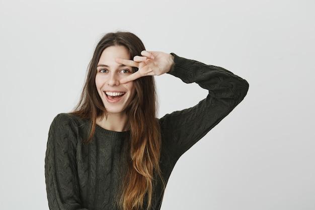 Freche gutaussehende frau, die friedenszeichen zeigt und zuversichtlich lächelt