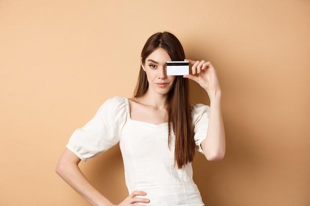 Freche junge frau, die plastikkreditkarte im gesicht zeigt und entschlossen aussieht, als sie auf den einkaufsstand geht...