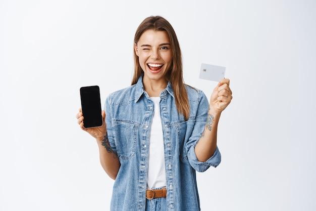 Freche junge frau zwinkert ihnen zu, empfiehlt mobile banking-app, zeigt leeren smartphone-bildschirm und plastikkreditkarte, weiße wand
