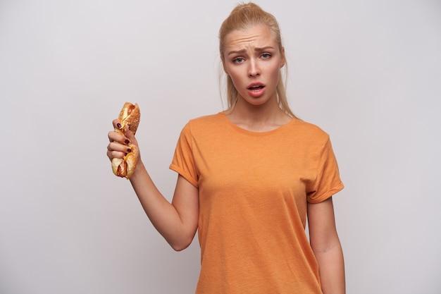 Freche junge langhaarige blonde frau mit pferdeschwanzfrisur, die trotzig in die kamera schaut und die augenbrauen runzelt, zerschlagenen hot dog in der erhobenen hand hält, während sie über weißem hintergrund steht