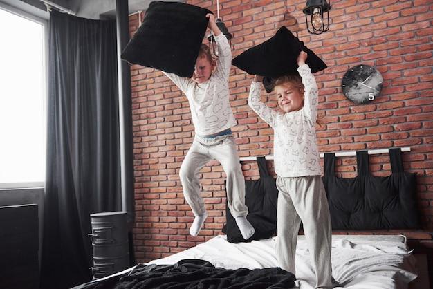 Freche kinder kleiner junge und mädchen veranstalteten eine kissenschlacht auf dem bett im schlafzimmer. sie mögen diese art von spiel