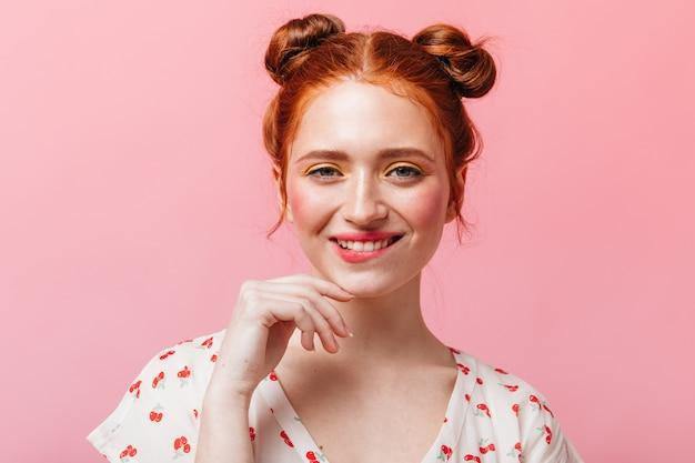 Freche rothaarige dame mit hellem make-up zwinkert und lächelt auf rosa hintergrund.