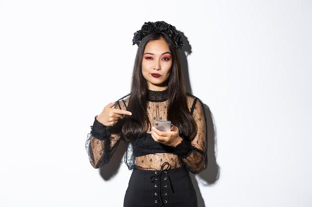Freche schöne asiatische frau im gotischen kleid und im schwarzen kranz, der finger auf handy zeigt und etwas über halloween zeigt