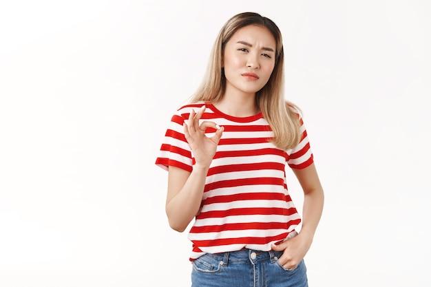 Freche selbstbewusste gutaussehende durchsetzungsfähige junge herrische blonde asiatin, die ernsthafte zustimmung schielt gesicht zeigen okay ok ausgezeichnete arbeit gut gemachte geste, stehende weiße wand
