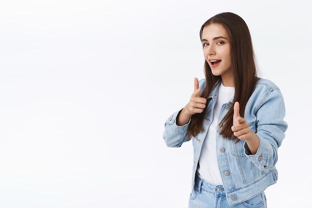 Freche, stylische und coole attraktive brünette frau in jeansjacke, fingerpistolen-kamera zeigend und kokett aussehende kamera, edel wirken, um jemanden zu ermutigen, promo auszuchecken, weißer hintergrund