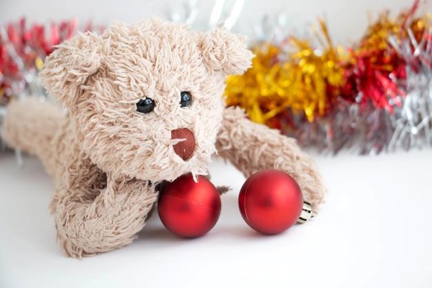 Freche teddybär spielt eine rote kugel schmücken weihnachtsbaum