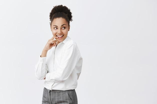 Freche und nachdenkliche afroamerikanerfrau, die erfreut lächelt, über große geschäftsidee nachdenkt und richtig schaut