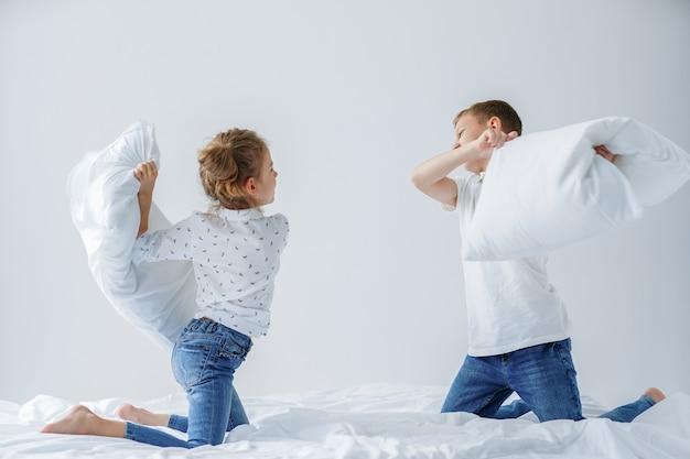 Freche zwillinge kämpfen freundlich mit kissen auf dem bett
