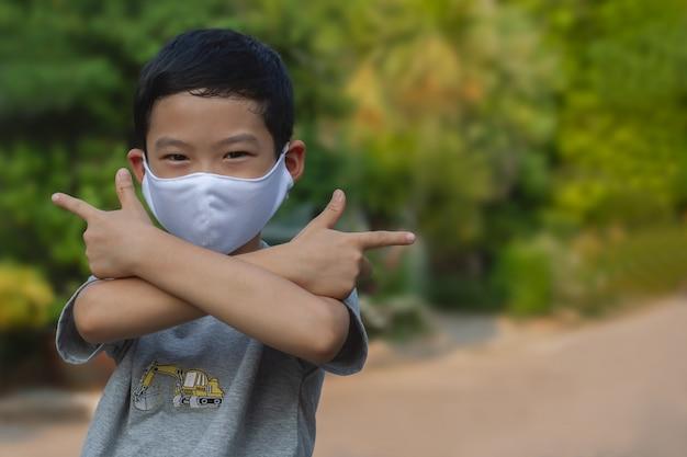 Frecher asiatischer junge des schwarzen haares tragen eine weiße schützende gesichtsmaske und bereiten sich auf den kampf auf unscharfem hintergrund im freien vor. bild für pm 2.5 mikrostaubverschmutzung oder covid-19-geschütztes konzept.