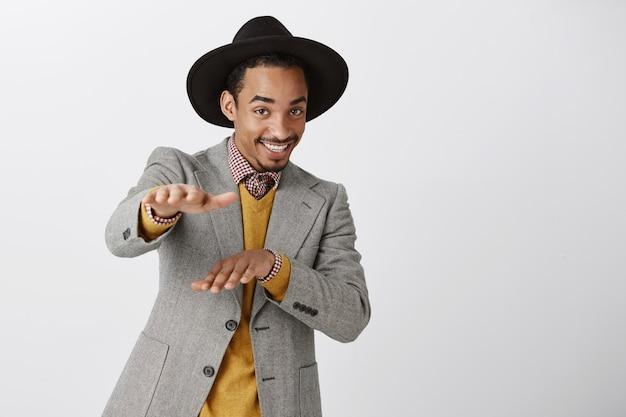 Frecher gutaussehender afroamerikanischer mann im anzug tanzt und lächelt glücklich