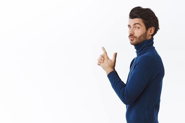 Frecher, gutaussehender mann in stylischem pullover mit hohem kragen, der im profil vor der kamera steht, mit durchsetzungsfähigem, frechem ausdruck, der fingerpistole macht, spion oder geheimagent nachahmt, weiße wand stehend