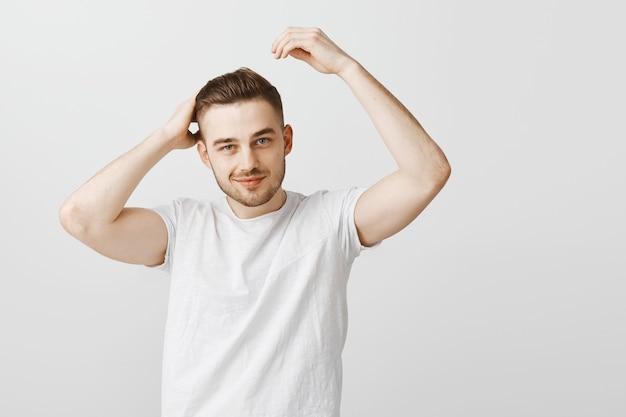 Frecher gutaussehender mann zufrieden mit neuem haarschnitt nach friseurladen