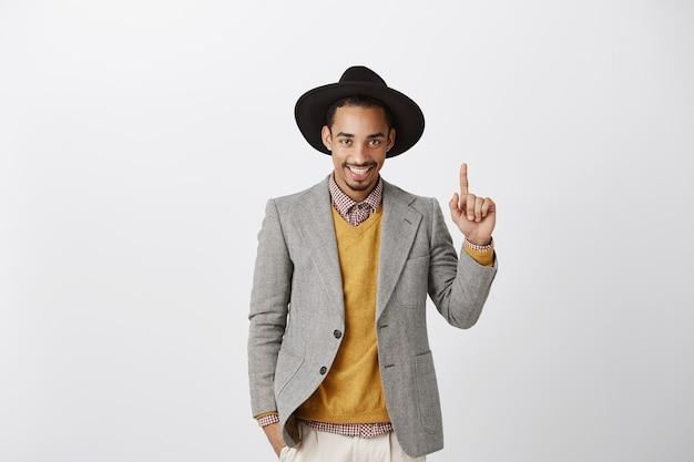 Frecher hübscher afroamerikanischer geschäftsmann im anzug, der finger nach oben zeigt und nummer eins zeigt