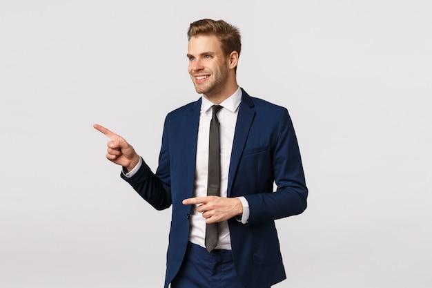 Frecher, überzeugter reicher und erfolgreicher männlicher unternehmer, kaukasischer blonder mann in der klassischen klage, nach links zeigend und schauen und lächeln erfreut und sehen wundervolles produkt, nach genau was suchen