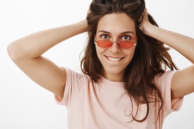 Freches attraktives mädchen mit sonnenbrille, die gegen die weiße wand aufwirft