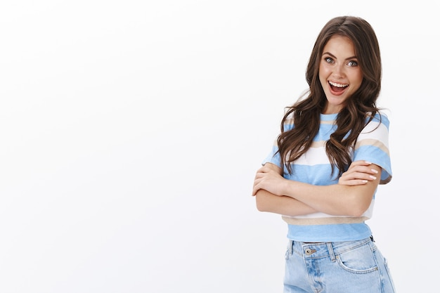 Freches, gesundes und energiegeladenes, gut aussehendes brünettes mädchen in t-shirt und jeans, ehrgeizige, selbstbewusste pose der brust mit verschränkten armen, amüsiert lächeln, überrascht und fröhlich aussehen, tolle angebote diskutieren, sich freuen