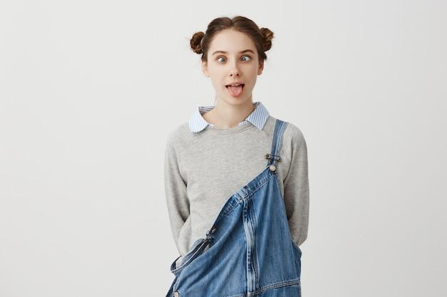 Freches junges mädchen mit doppelbrötchen mit zusammengekniffenen augen, die zum spaß ihre zunge herausstrecken. weibliche junge schauspielerin, die vorgibt, ein kleiner dummkopf zu sein, der gesicht macht, das jeansoveralls trägt.