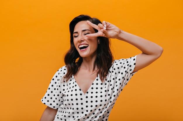 Freches mädchen lacht und zeigt friedenszeichen auf orange hintergrund. charmante brünette in weißen gepunkteten kleidern lächelt und hat spaß.