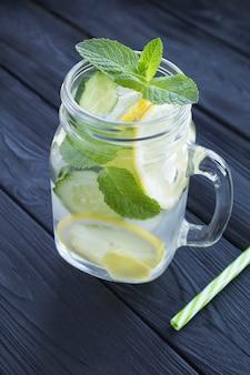 Freches wasser abnehmen oder wasser mit zitrone, gurke und ingwer in das glas auf dem schwarzen hölzernen hintergrund hineingegossen. lage vertikal.