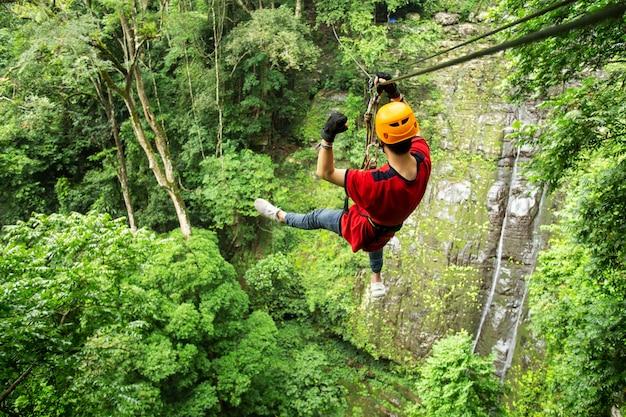 Freedom adult man tourist trägt freizeitkleidung auf zip line oder canopy experience