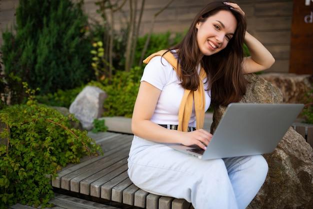 Freelancer der glücklichen frau auf kaffeepause, die draußen auf einer bank ruht.
