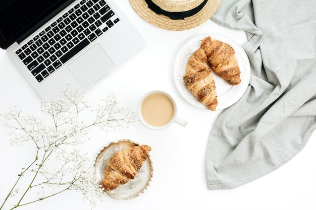 Freelancer-home-office-schreibtischarbeitsplatz mit laptop und decke. morgens frühstück mit kaffee und croissant. flache lage, ansicht von oben