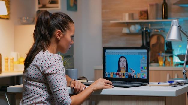Freelancer-retuschierfrau, die an laptop-computer mit bildbearbeitungssoftware arbeitet. professioneller grafikeditor, der fotos eines kunden während der nachtzeit im home office auf einem performance-pc retuschiert.